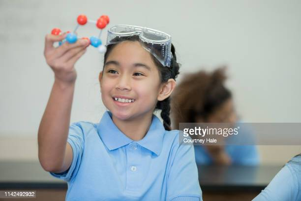asian ethnicity junior high school girl enjoying stem science class and examining a molecule model - junior girl models stock pictures, royalty-free photos & images