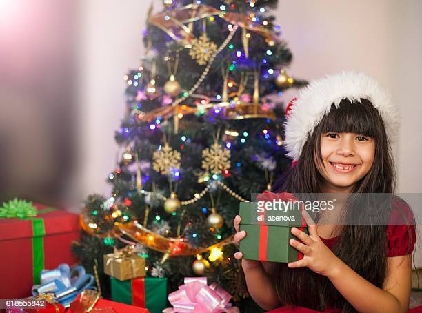 Asian excited little girl holding gift box on Christmas day
