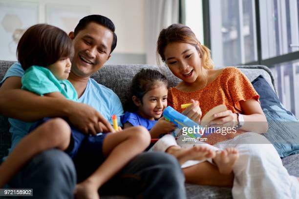 asian family bonding at home - muslim couple stock pictures, royalty-free photos & images