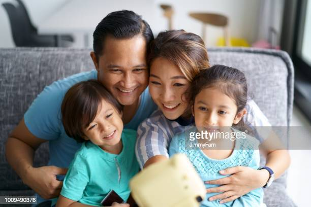 asian family bonding at home with a polaroid camera - southeast stock pictures, royalty-free photos & images