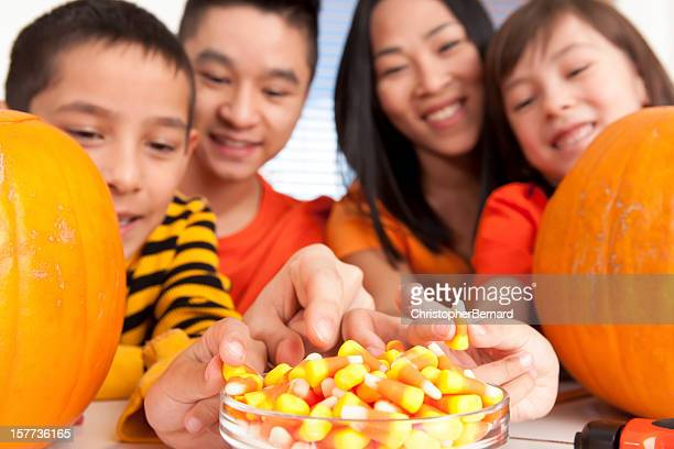 asian family carving pumpkin - candy corn stock photos and pictures