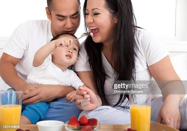 Asian family eating breakfast in bed