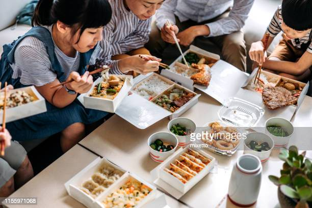 asian family eating takeout food in living room - chinese takeout stock pictures, royalty-free photos & images