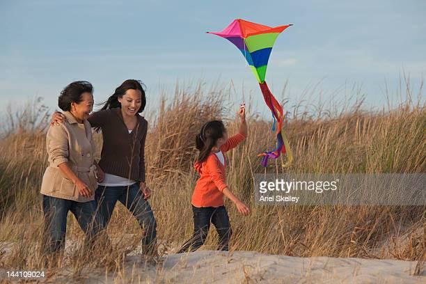 Asian family flying kite on beach