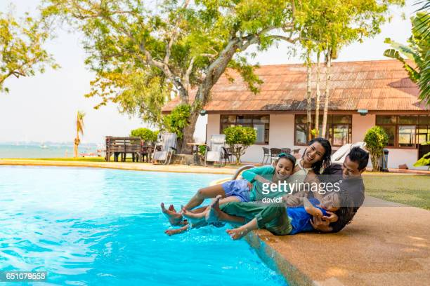 Asian Family Having Fun by the Pool on a Resort Vacation