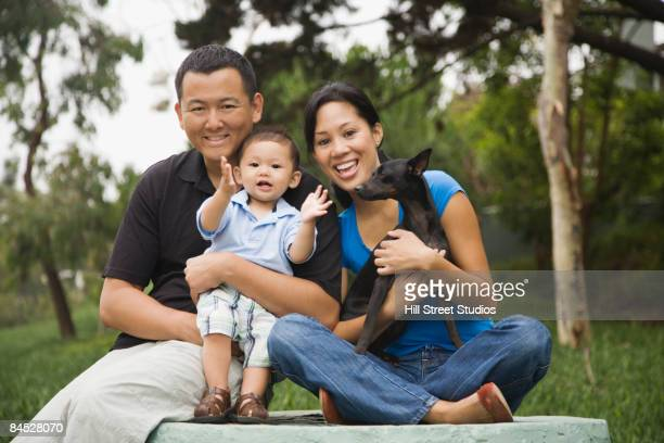 Asian family in park with dog