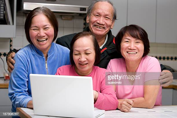 Asian Family Laughing and Smiling, Using Laptop in Home Kitchen