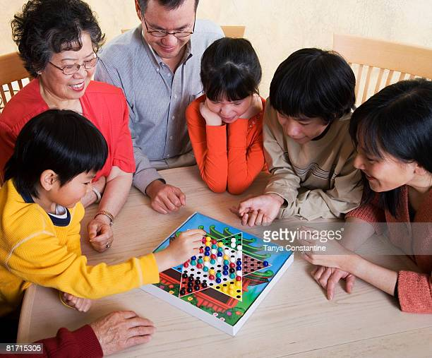 Asian family playing board game