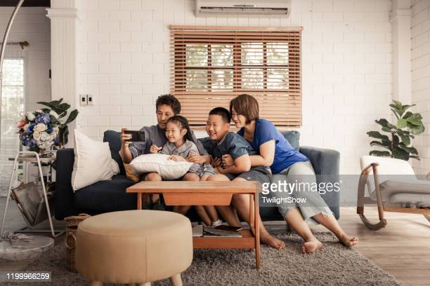 asian family playing together at home with happiness - family at home stock pictures, royalty-free photos & images