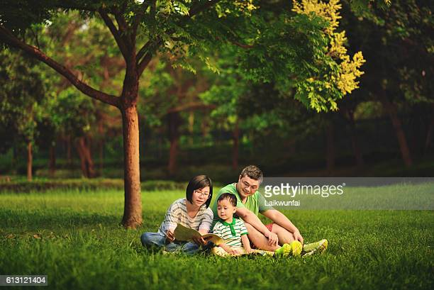 Asian family reading outdoor
