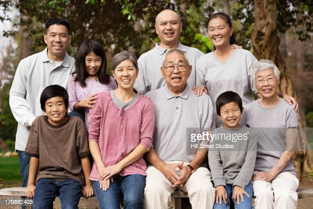 asian family smiling together outdoors - chinese family stock photos and pictures
