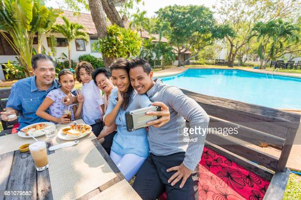 Asian Family Taking Selfie Self Portraits While Eating at a Resort