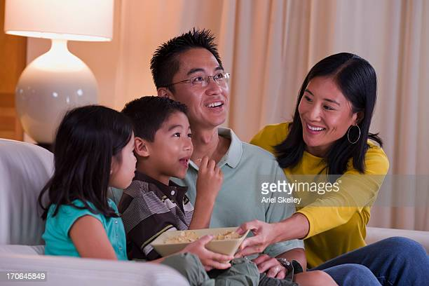 Asian family watching television together