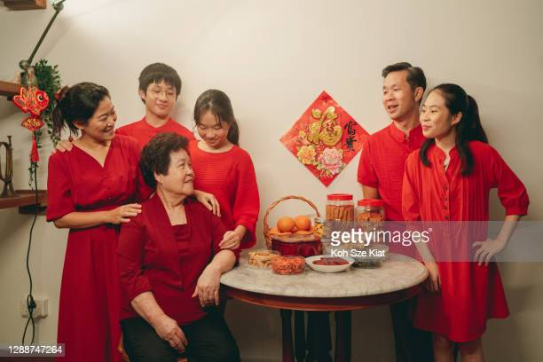 asian family wearing red candidly standing around a table with chinese new year table before taking the family portrait photo - chinese new year stock pictures, royalty-free photos & images