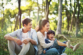 asian family with one child having fun in the woods