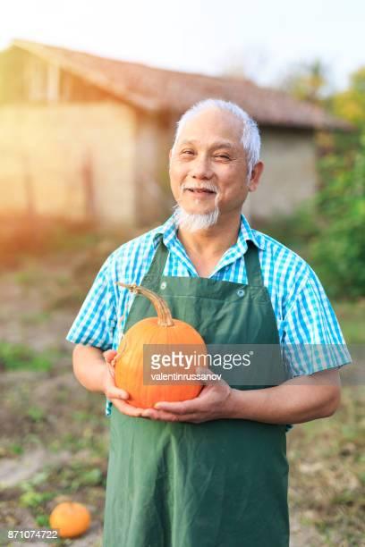 Asian farm worker holding a pumpkin