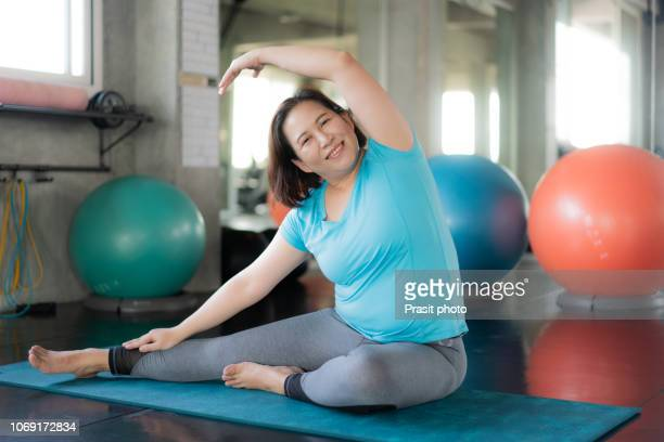 asian fat woman doing yoga exercise in gym. - chubby asian woman stock pictures, royalty-free photos & images
