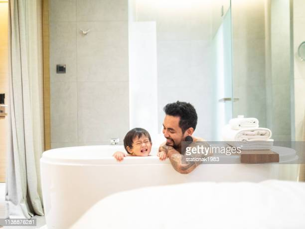 asian father and baby son having fun at bath time together - boys taking a shower stock pictures, royalty-free photos & images