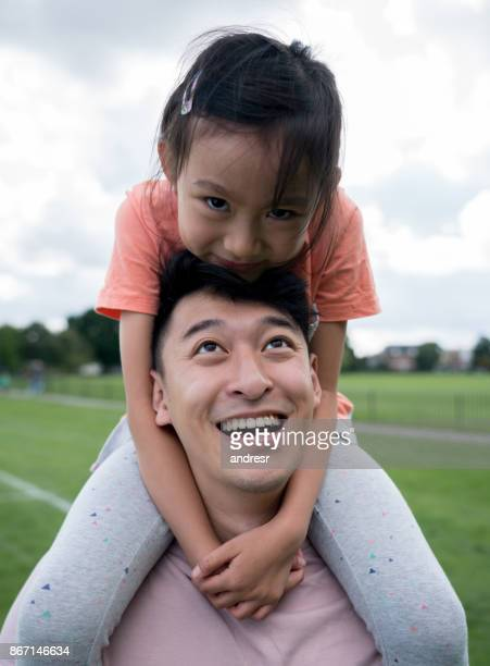 Asian father and daughter having fun at the park