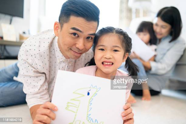 asian father and daughter holding up a drawing - prop stock pictures, royalty-free photos & images