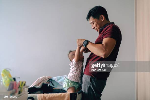 asian father enjoys the time spent with his baby girl during diaper changing - baby changing mat stock pictures, royalty-free photos & images