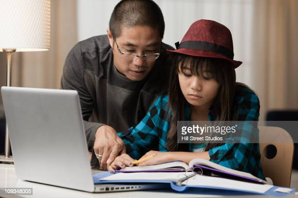 Asian father helping daughter with her studies