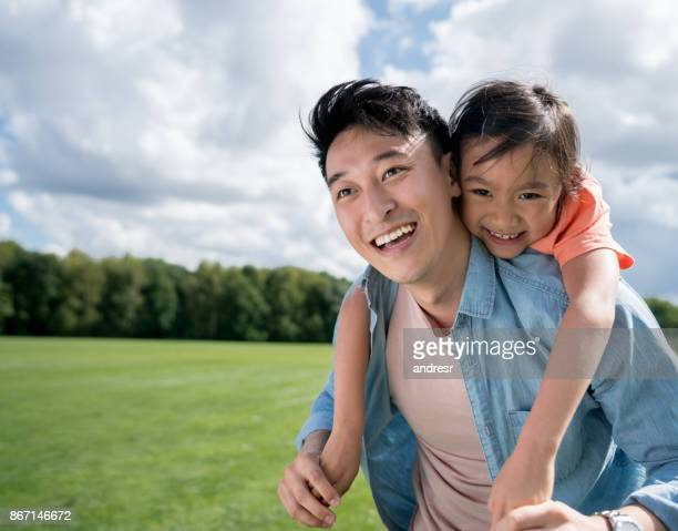 asian father looking very happy playing with his daughter at the park - asia stock pictures, royalty-free photos & images