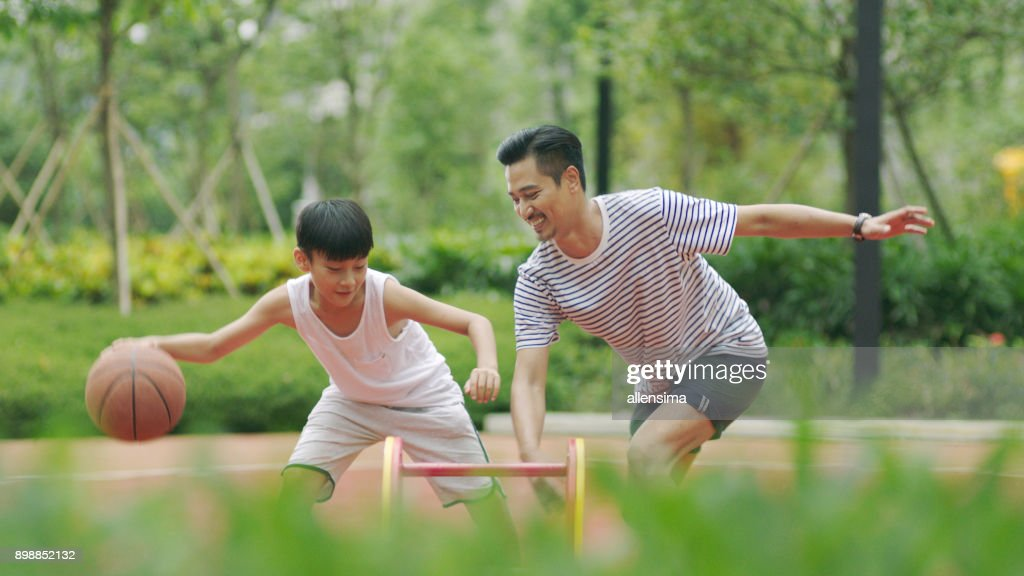 Asian father & son playing basketball in garden in morning : Stock Photo