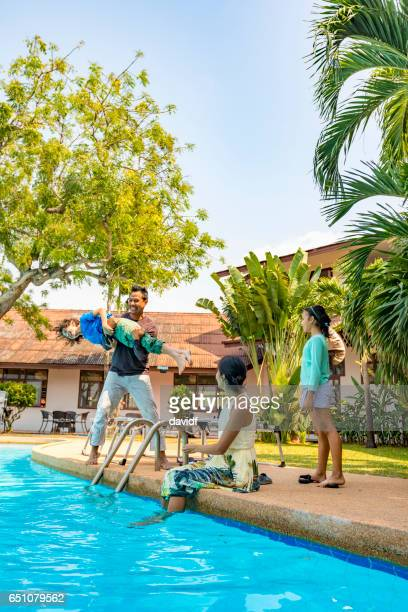 Asian Father Throwing His Son in the Pool on a Resort Vacation