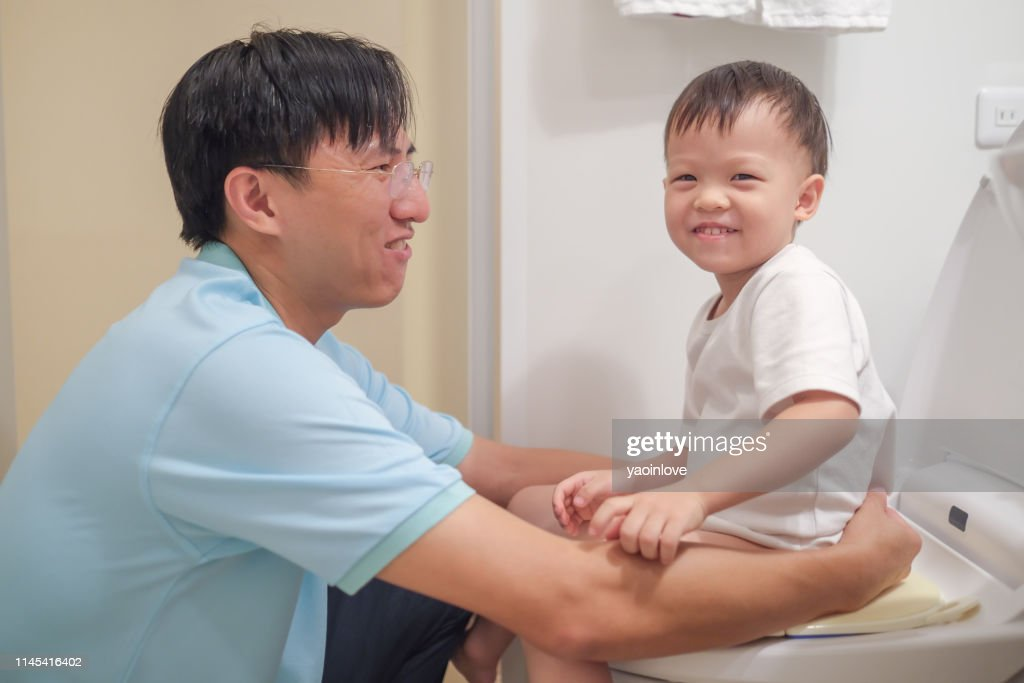 Asian Father Training 2 years old son to use toilet in bathroom, Kid sitting on toilet with kid bathroom accessory, Toilet training concept : Stock Photo