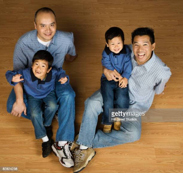 asian fathers holding sons in lap - uncle stock photos and pictures