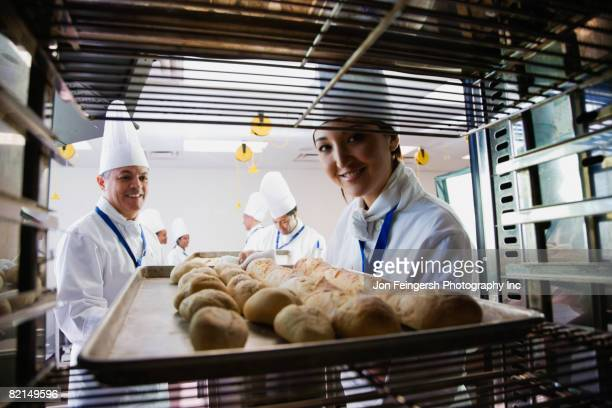 Asian female baker taking tray of bread off rack