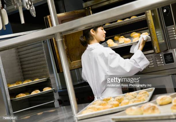 Asian female chef checking tray of bread