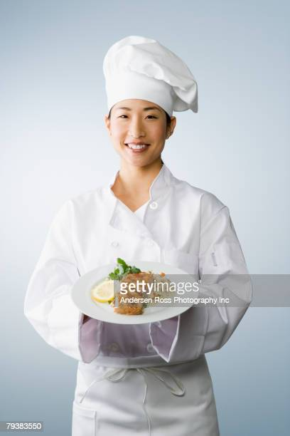asian female chef holding plate of food - chef's hat stock pictures, royalty-free photos & images