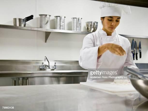 Asian female chef sprinkling flour on dough