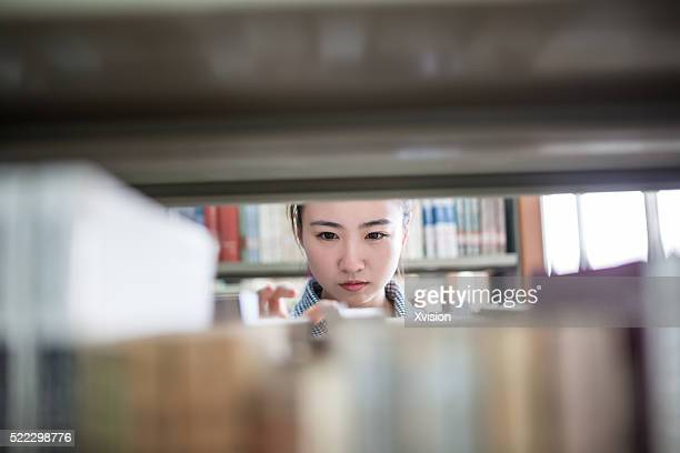 Asian female college student reading book in the library
