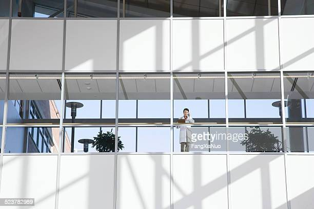 asian female doctor on the phone - hospital building stock photos and pictures