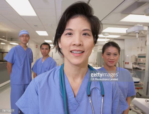 Asian female doctor smiling with co-workers in background