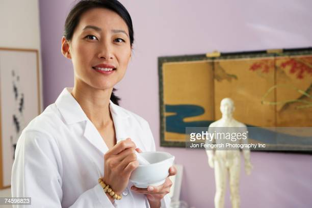 asian female doctor using mortal and pestle - anatomical model stock pictures, royalty-free photos & images