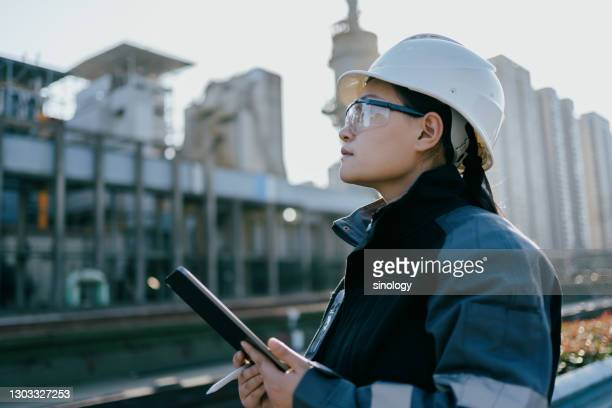 asian female engineer working in factory with tablet - examining stock pictures, royalty-free photos & images