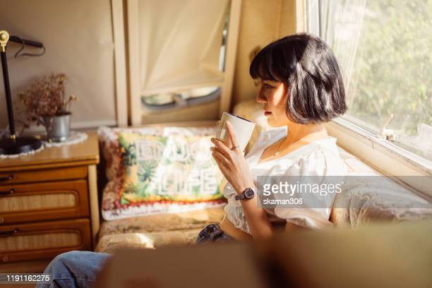 asian female feeling happy and relax and drink coffee on camper vans - café culture agricole photos et images de collection