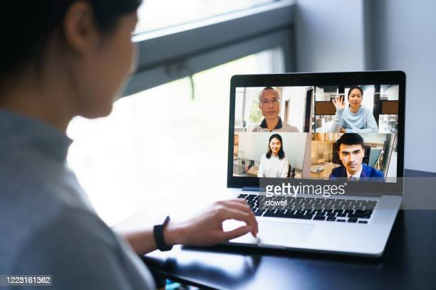 asian female having conference call on laptop - video conference stock pictures, royalty-free photos & images