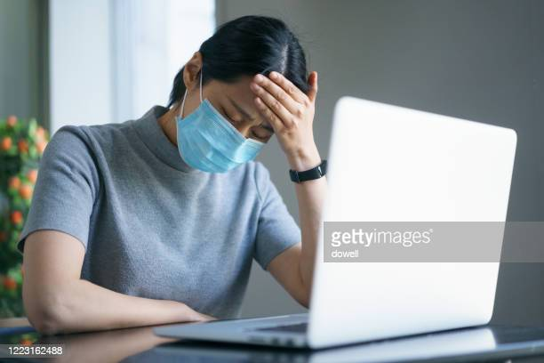 asian female headache while working on laptop with face mask - お面 ストックフォトと画像