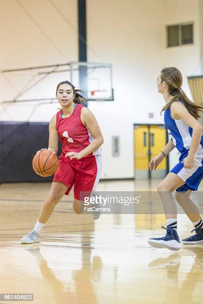 Asian female high school athlete dribble basketball around opposing player in game