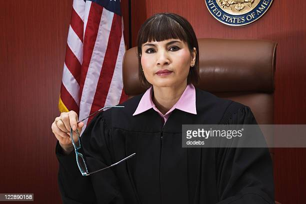 asian female judge seated in courtroom - judge stock pictures, royalty-free photos & images