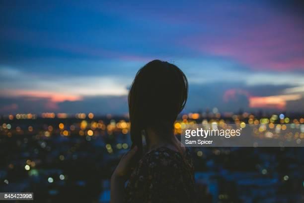 asian female looking at beautiful night city skyline, asia - 見渡す ストックフォトと画像
