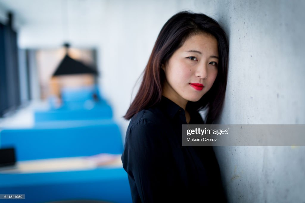 Asian Female Model Standing Against Grey Industrial Wall Stock Photo