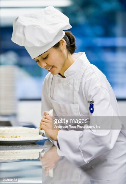 Asian female pastry chef decorating dessert