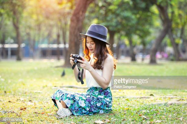 Asian female photographer is sitting on grass and looking camera in a beautiful green forest.