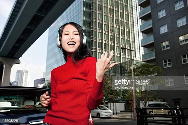 Asiatische Frau spielt Luftgitarre spielen